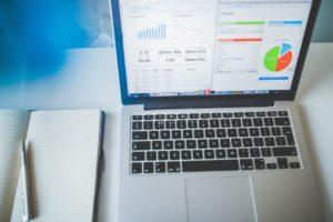 Wykresy analityki internetowej na laptopie.